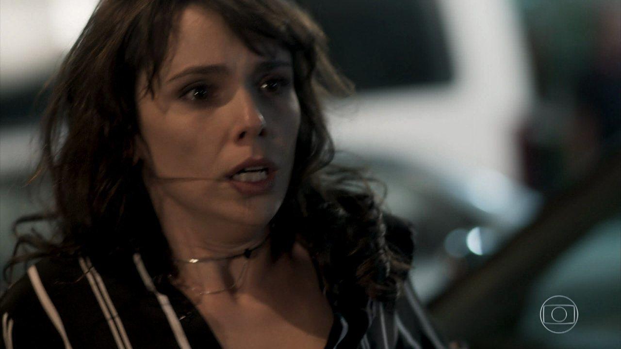 Irene, mulher branca com cabelos médios escuros e camisa listrada preta e branca, está em uma cena na rua à noite na novela A Força do Querer