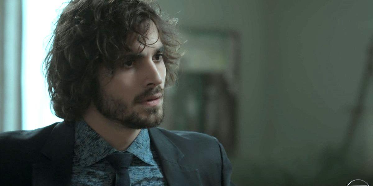 Ruy em cena da novela A Força do Querer com expressão de bravo e usando terno e gravata em tons escuros