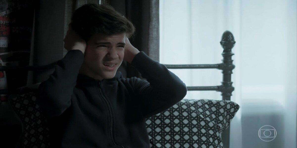 Yuri, adolescente menino, branco está tampando as orelhas com as mãos em cena da novela A Força do Querer