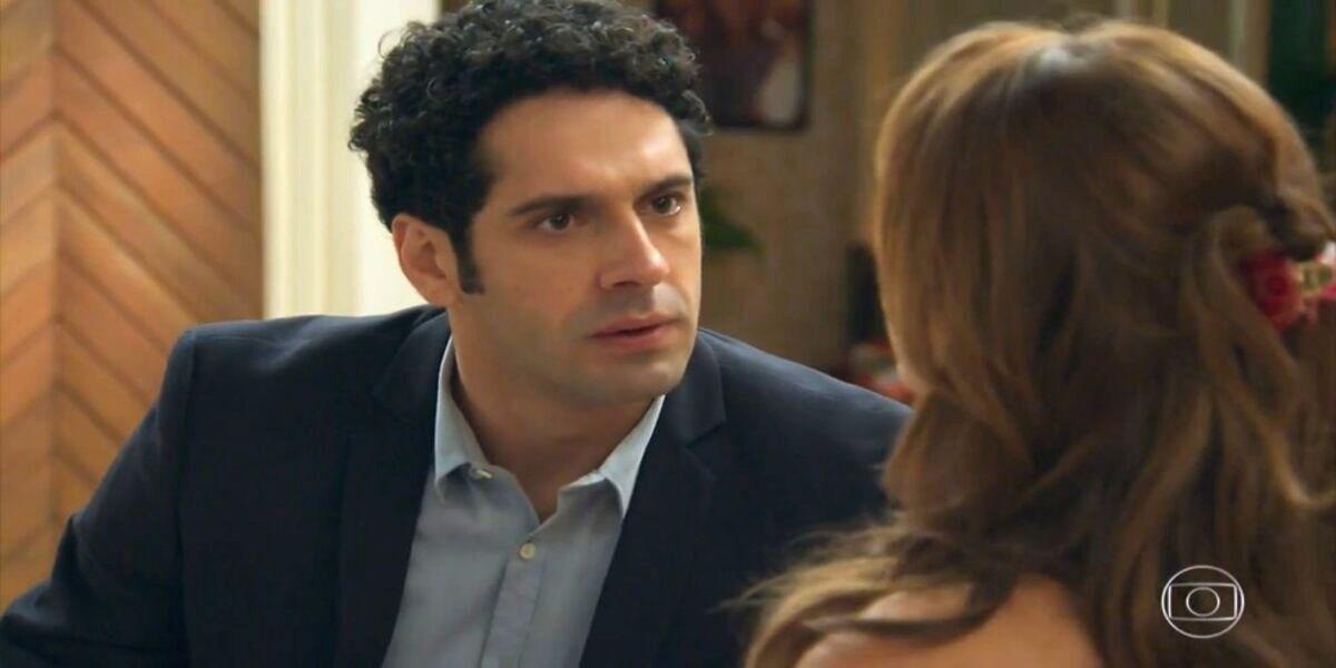 Beto, homem branco de cabelo cacheado, está de terno e camisa azuis em cena da novela Haja Coração