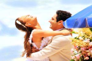 João Baldasserini e Mariana Ximenes vestidos de noivo e noiva em cena de Haja Coração gravada na praia de dia