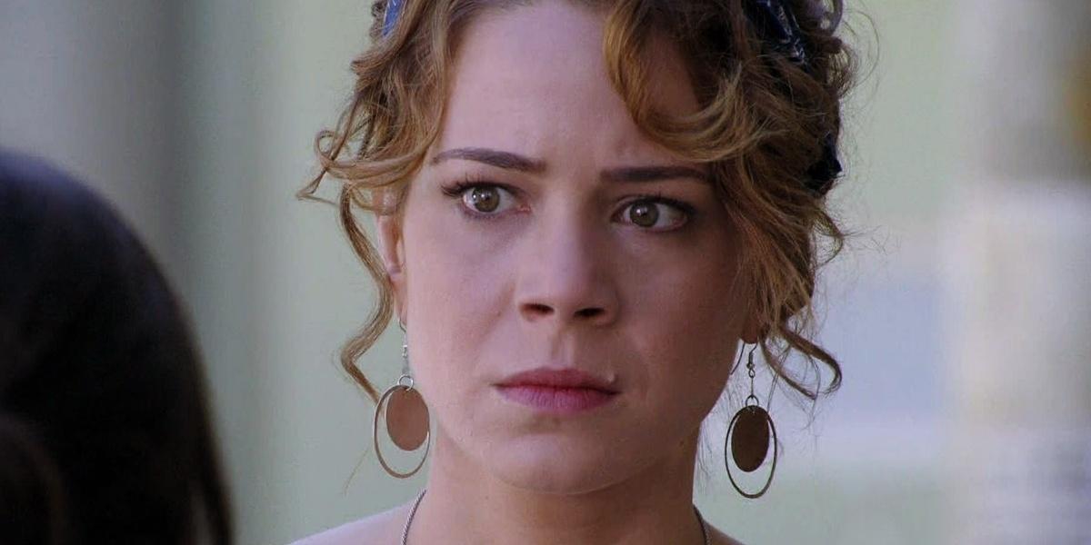 Cristian em cena de Império, mulher branca, de cabelo cacheado loiro amarrado e brincos grandes redondos