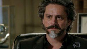 José Alfredo, homem mais velho com barba e cabelos grisalhos e preto com terno preto em cena da novela Império