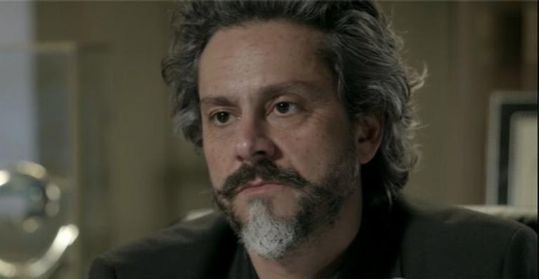 José Alfredo, homem mais velho com barba branca e preta, cabelos grisalhos e terno preto em cena da novela Império