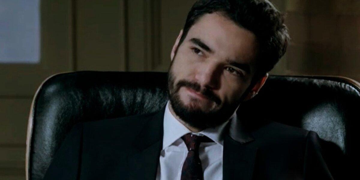 José Pedro em cena de Império onde usa terno e gravatas pretos com camisa social branca