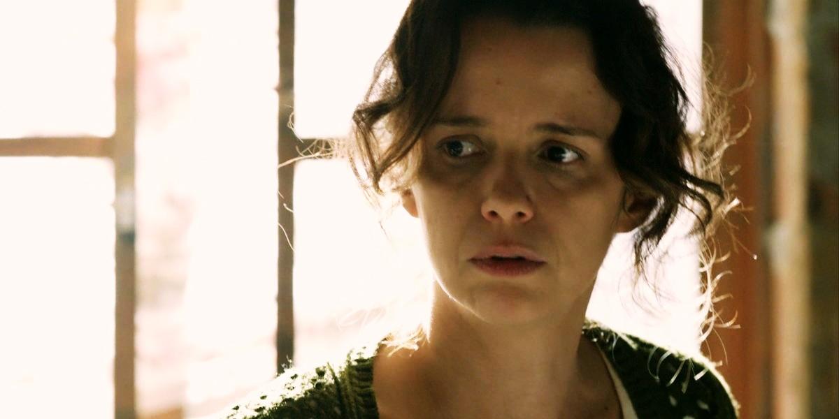 Lorraine usando casaco verde de trico, em contra luz da janela em cena de Império