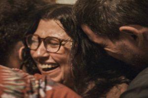 Lurdes sendo abraçada enquanto sorri usando óculos na novela Amor de Mãe