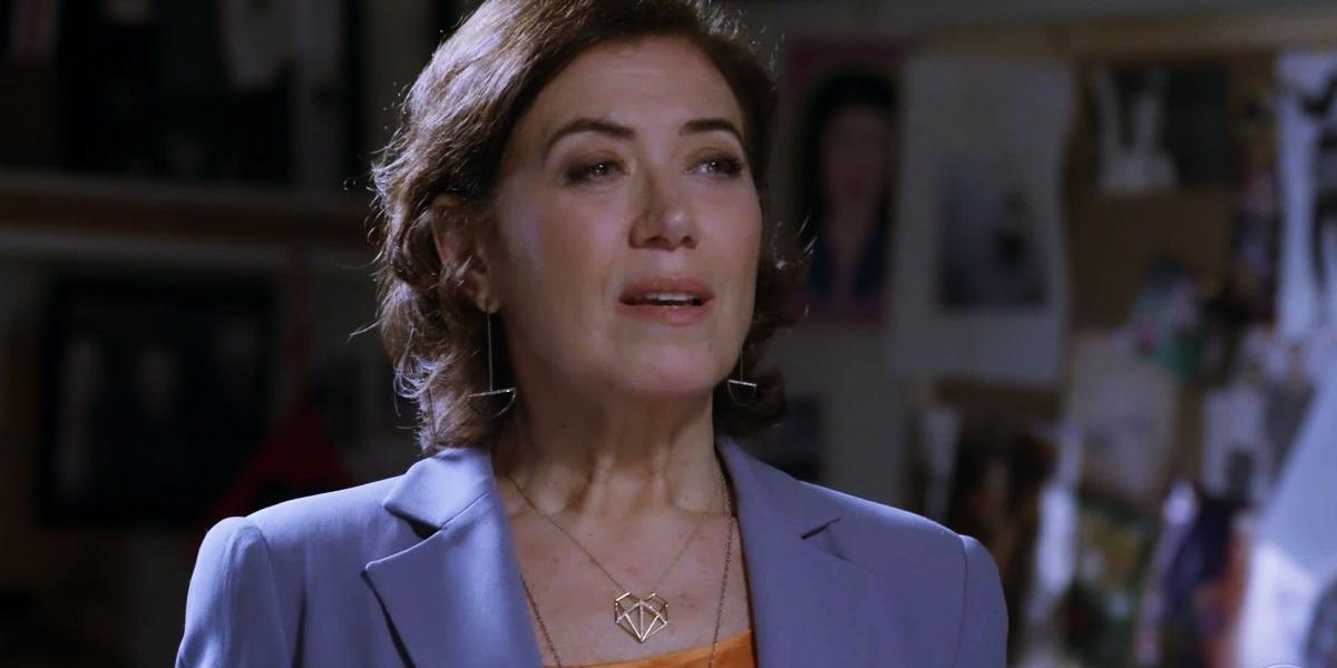 Em cena da novela Império maria marta usa blusa laranja, terno acinzentado e um colar