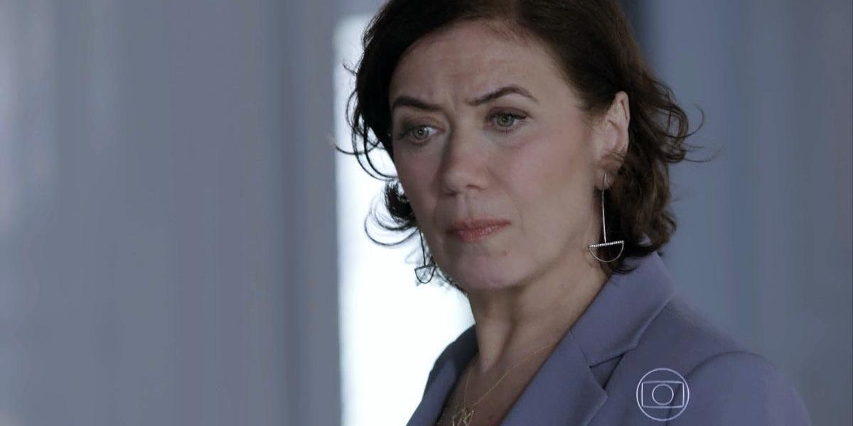Maria Marta, mulher branca, de olhos azuis, usa terno cinza e cabelos curtos, lisos e castanhos em cena da novela Império