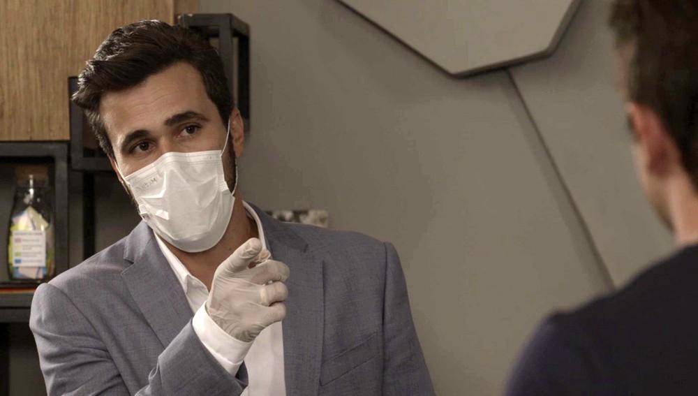 Rafael em cena de Salve-se Quem Puder com terno cinza, luvas e máscara no rosto