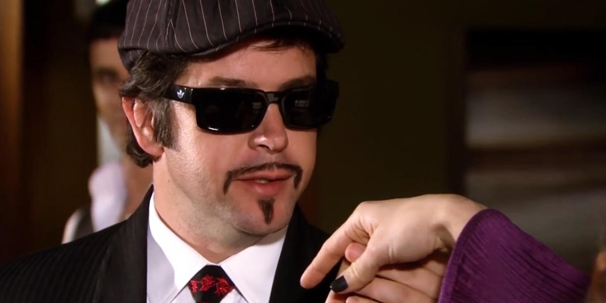 Victor Valentim em cena de Ti-Ti-Ti com boina, óculos escuros, camisa branca e gravata com detalhes vermelhos