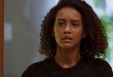 Vitória usando camiseta preta, mulher negra com cabeços cacheados em cena de Amor de Mãe