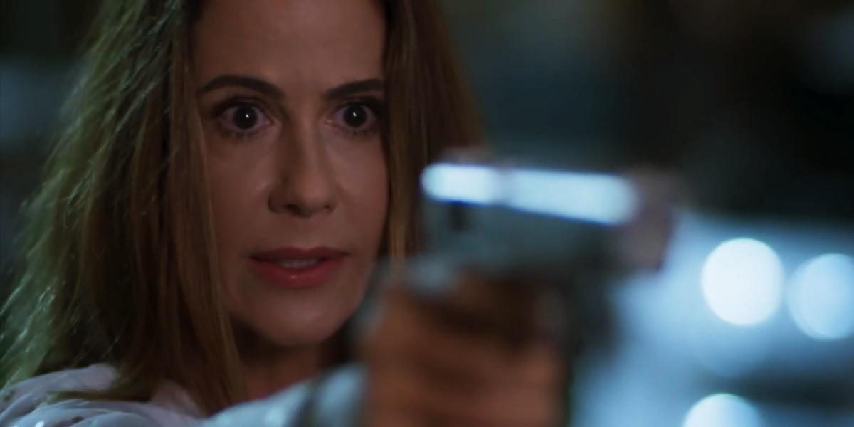 Dominique em cena noturna de Salve-se Quem Puder apontando um revólver